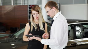 Female customer shop consultant tells about automobile in car centre stock video footage