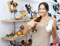 Female customer showing desired shoe in boutique. Beautiful young female customer showing desired shoe in boutique Royalty Free Stock Photos