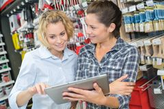 Female customer showing digital tablet to vendor in hardware store stock images