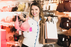 Female customer showing her purchases in underwear shop. Happy spanish female customer showing her purchases in underwear shop royalty free stock image