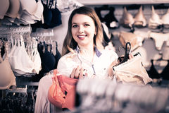 Female customer showing her purchases in underwear shop Royalty Free Stock Image