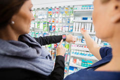Female Customer Showing Smartwatch To Pharmacist Stock Photo