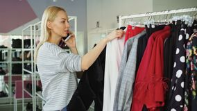 Female customer is slowly going through fashionable clothes on hanger in spacious shop. Other customers are moving