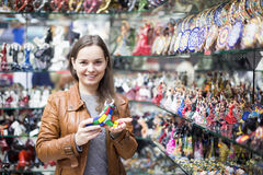 Female customer in souvenir shop. Smiling girl in leather jacket choosing things for memory in souvenir shop Stock Photo