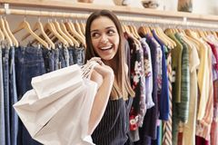Female Customer Standing By Racks Of Clothes In Independent Fashion Store Holding Bags royalty free stock photo
