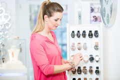 Female customer in store looking for wristwatches Royalty Free Stock Images