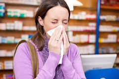 Female Customer Suffering From Cold In Pharmacy Stock Photography