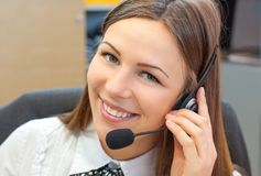 Female customer support operator with headset. And smiling Royalty Free Stock Images