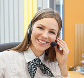 Female customer support operator with headset. And smiling Royalty Free Stock Photography