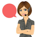 Female customer support phone operator with arms crossed and speech bubble. Portrait of female customer support phone operator with arms crossed and speech Royalty Free Stock Photos