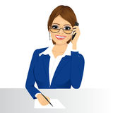 Female customer support phone operator. Portrait of happy smiling female customer support phone operator with glasses taking note isolated over white background Stock Photography