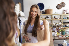 Female customer takes bag from shop assistant in a boutique Royalty Free Stock Images