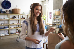 Female customer takes bag from shop assistant in a boutique Stock Images