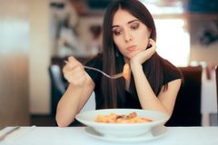 Female Customer Unhappy with the Dish Course in Restaurant. Depressed lonely woman suffering from appetite loss Stock Image