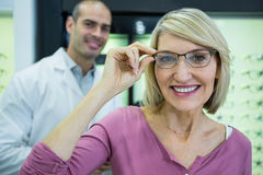 Female customer wearing spectacles in optical store Stock Images