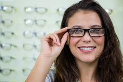 Female customer wearing spectacles in optical store Royalty Free Stock Images
