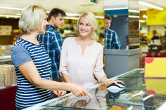 Female customers near display with frozen food. Female customers standing near display with a frozen food at the supermarket Stock Image