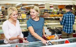 Female customers near display with frozen food Stock Photo