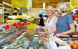 Female customers near display with frozen food Stock Photos