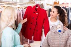 Female customers selecting coats and jackets. Attractive young female customers selecting coats and jackets at the shop Royalty Free Stock Photo