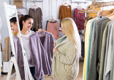 Female customers selecting coats and jackets Stock Images