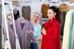 Female customers selecting coats and jackets. Positive young female customers selecting coats and jackets at the store. Focus on the right woman Stock Photography