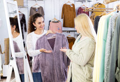 Female customers selecting coats and jackets Stock Image