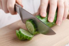 Female cut raw cucumber on cutting board Royalty Free Stock Photos
