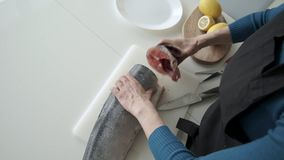 Female cutting fish with a knife in the kitchen. Top view.  stock video
