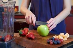 Female cutting fresh fruits Royalty Free Stock Photo