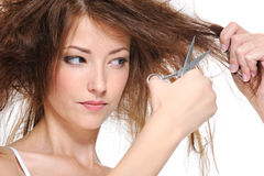 Female cutting her backcombing brunette hair Royalty Free Stock Images