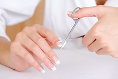 Female cutting nail on the  index finger Royalty Free Stock Photography