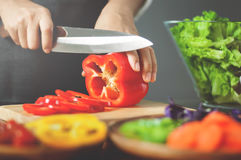 Female cutting red bell peppers. Cooking vegan food. healthy wit. H vegetables Royalty Free Stock Photography
