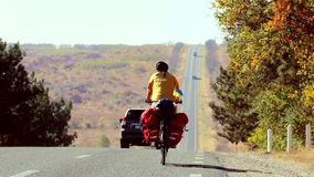 Cyclist on the road. Female cycling traveler going straight along the road in Ukraine stock video