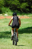 Female cyclist. An active female mountain biker riding her bicycle in nature Royalty Free Stock Photo