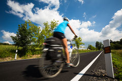 Female cyclist biking on a country road Royalty Free Stock Photos
