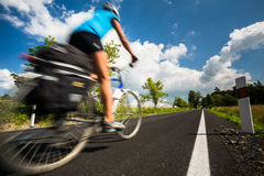 Female cyclist biking on a country road Royalty Free Stock Photo