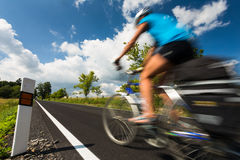 Female cyclist biking on a country road Stock Photo