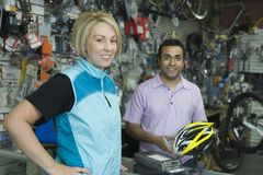 Female cyclist buying helmet at bike shop Royalty Free Stock Photo