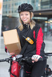 Female Cyclist With Cardboard Box And Courier Bag Stock Photography