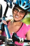 Female cyclist carrying her bike Royalty Free Stock Photography