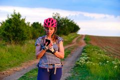 Free Female Cyclist Checking Her Phone For Directions On An MTB Route In The Countryside, At Sunset. Royalty Free Stock Photography - 149335807