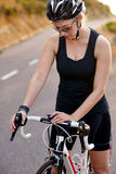 Female cyclist checking time Royalty Free Stock Photos