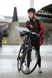 Female Cyclist With Courier Bag And Package On Stock Image