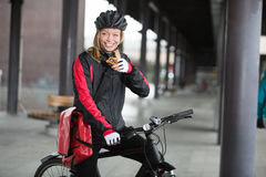 Female Cyclist With Courier Bag Using Stock Image