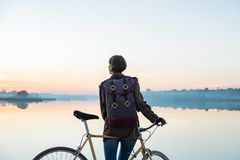 Female cyclist enjoying beautiful blue hour scene by the lake. W royalty free stock images