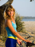Female cyclist posing outdoors. Young female blond cyclist staying looking to camera smiling Royalty Free Stock Photos
