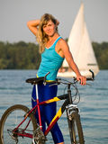 Female cyclist posing outdoors. Young female blond cyclist staying looking to camera smiling Royalty Free Stock Photo