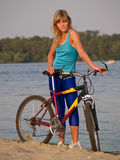 Female cyclist posing outdoors. Young female blond cyclist staying looking to camera smiling Stock Images