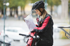 Female Cyclist Putting Package In Courier Bag Stock Photo